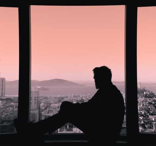 Un homme regarde l'horizon à travers une fenêtre et se soigne grâce à la Psychothérapie