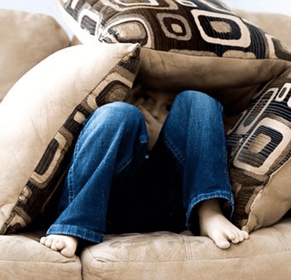 Un enfant sous des cousins angoissé et avec le l'anxiété